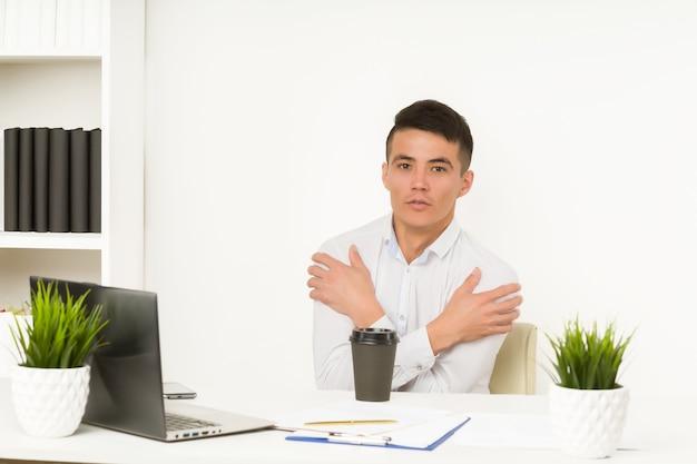 Asiatischer mann friert im büro ein, da die heizung oder kühlung der klimaanlage übermäßig unterbrochen ist