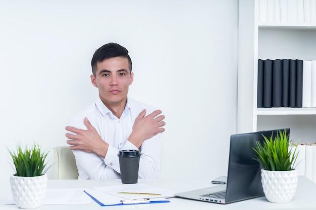 Asiatischer mann friert im büro seit defekter heizung oder kühlung der klimaanlage übermäßig ein - bild