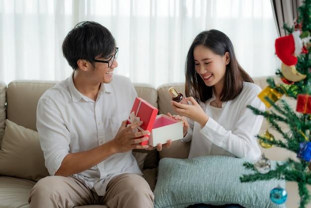 Asiatischer mann geben der frau eine rote geschenkbox, in der sich eine flasche parfüm befindet.