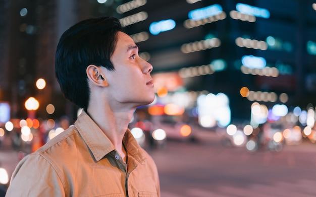 Asiatischer mann geht nachts auf der straße und fühlt sich verloren