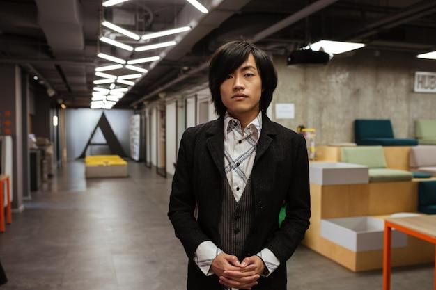 Asiatischer mann gekleidet in formelle kleidung, die drinnen steht