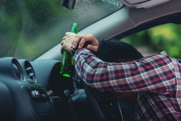 Asiatischer mann hält eine bierflasche, während ein auto fährt