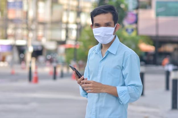 Asiatischer mann hält handy-smartphone verwenden sie gesichtsmaske schützen corona-virus pm2.5 gehen auf der straße neue normale soziale distanzierung