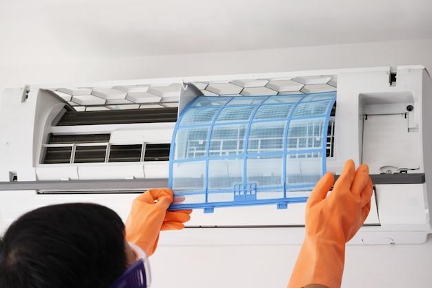 Asiatischer mann hand halten klimaanlage filter reinigungskonzept