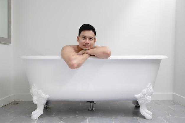 Asiatischer mann hat eine gute zeit in einer weißen badewanne.