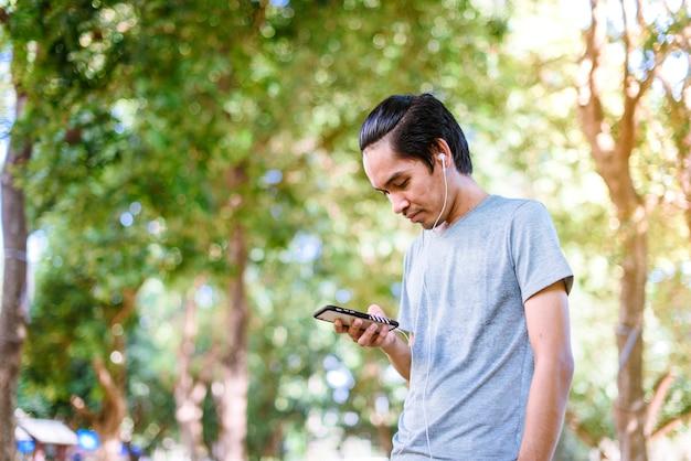 Asiatischer mann hat rest und hört musik während draußen laufen