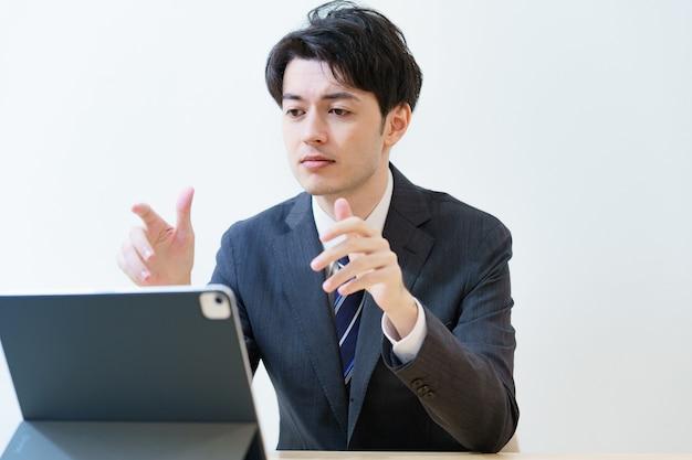 Asiatischer mann im anzug, der mit dem bildschirm eines tablet-pcs spricht