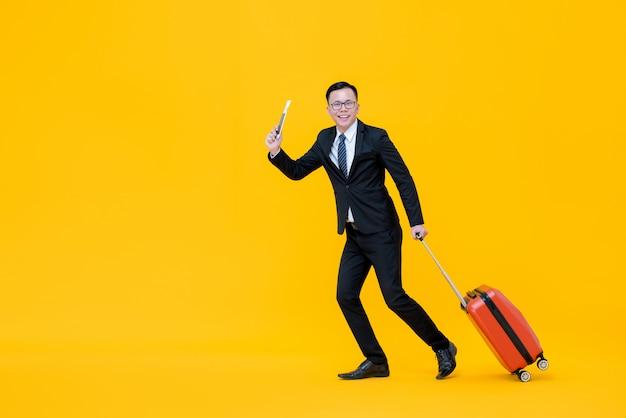 Asiatischer mann im formellen geschäftsanzug bereit zum reisen