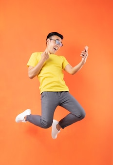 Asiatischer mann im gelben t-shirt, das auf orange wand springt
