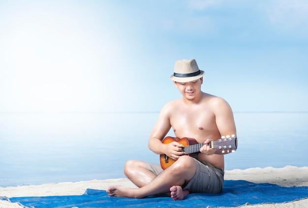 Asiatischer mann im hut, der gitarre auf dem teppich im strand sitzt und spielt