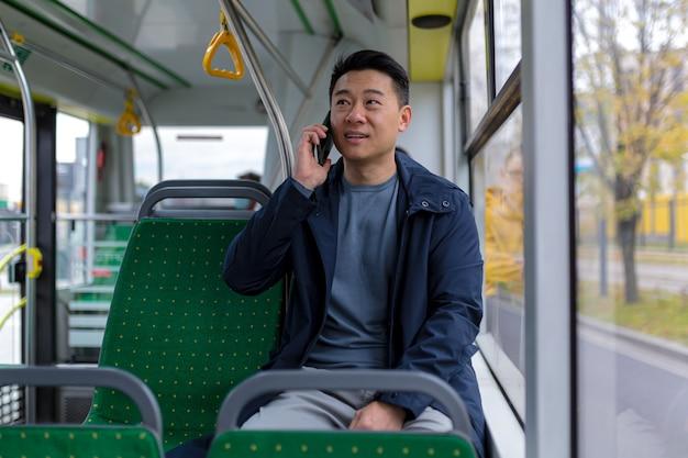Asiatischer mann im öffentlichen bus-passagier, der spaß am telefonieren hat, in freizeitkleidung