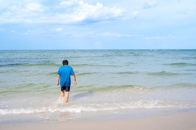 Asiatischer mann im rücken in lässigen tüchern, der vom strand ins meer geht, huhin beach in thailand, meerblick mit blauem himmel