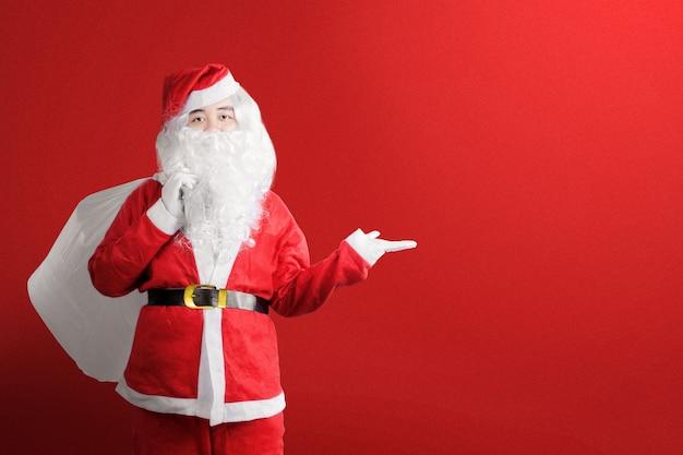 Asiatischer mann im weihnachtsmannkostüm mit einer offenen hand, die geschenktüte mit farbigen frohen weihnachten trägt