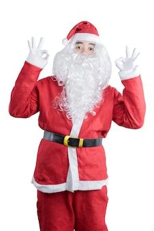 Asiatischer mann im weihnachtsmannkostüm mit ok-zeichengeste, die lokalisiert über weißem hintergrund steht
