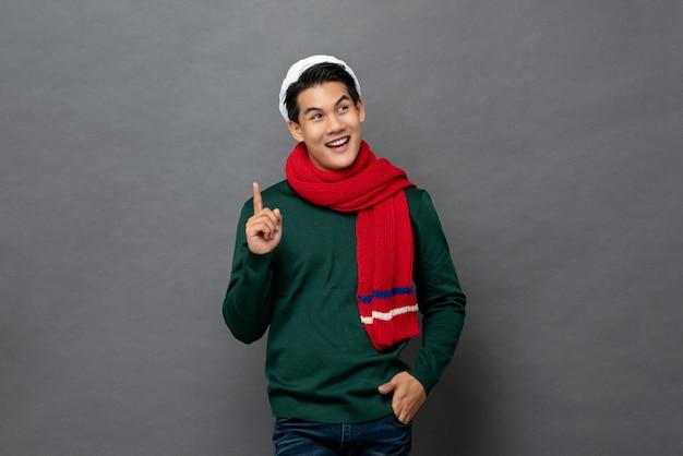 Asiatischer mann im weihnachtsmotiv kleidet raum beiseite denkend und betrachtend