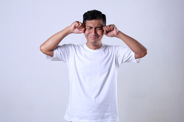Asiatischer mann im weißen t-shirt mit lustigem weinenden ausdruck auf weißem hintergrund