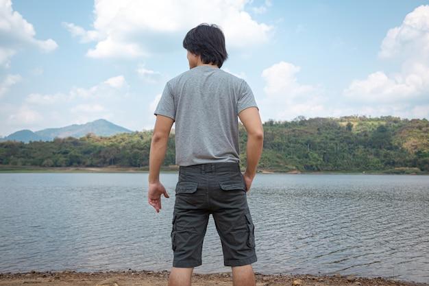 Asiatischer mann in bermudashorts und t-shirt, outdoor-aktivitätskonzept