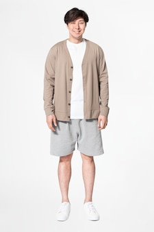 Asiatischer mann in brauner strickjacke und shorts bequemer loungewear-ganzkörper