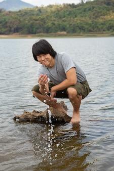 Asiatischer mann in den bermudashorts und im t-shirt, outdoor-aktivitätskonzept