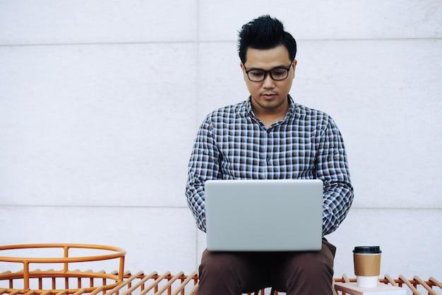 Asiatischer mann in den gläsern, die draußen auf bank sitzen und an laptop arbeiten