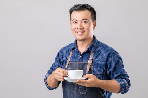 Asiatischer mann in der baristauniform, die kaffeetasse hält