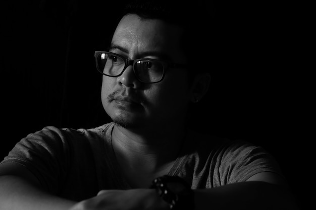 Asiatischer mann in der dunkelheit, die heraus das fenster schaut, schaut traurige stimmung