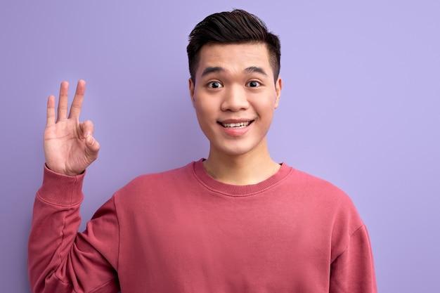 Asiatischer mann in der freizeitkleidung zeigt ok-geste an der kamera, lächelnd