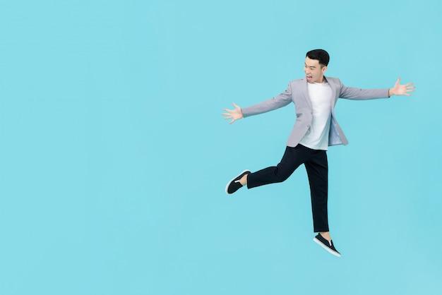 Asiatischer mann in der intelligenten zufälligen kleidung, die hände ausstreckt und mit begeisterung springt