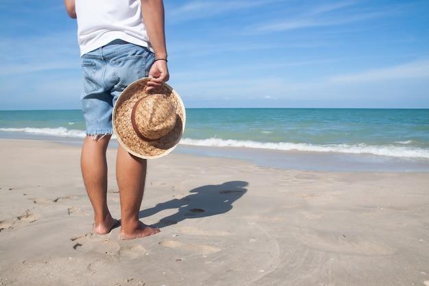 Asiatischer mann in der kleidung der zufälligen art, die strohhut hält, stehen auf dem strand