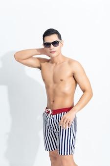 Asiatischer mann in der sommerkleidung trägt sonnenbrille.