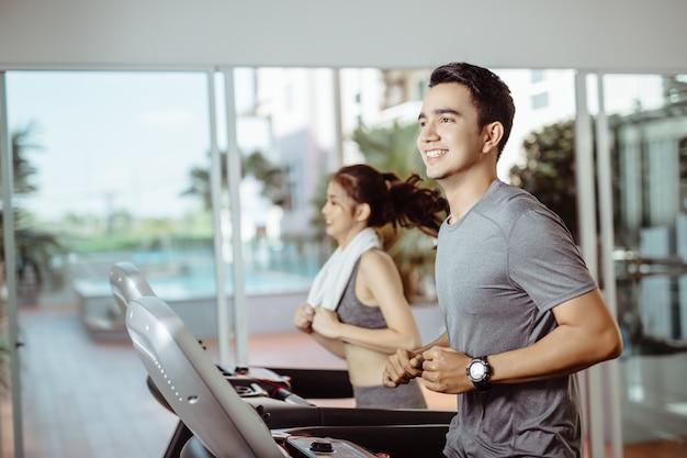 Asiatischer mann in der sportkleidung, die auf tretmühle an der turnhalle läuft