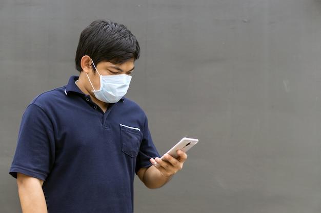 Asiatischer mann in der straße, die schutzmasken, kranken mann mit tragender maske der grippe trägt.