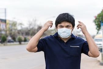 Asiatischer Mann in der Straße, die Schutzmasken trägt