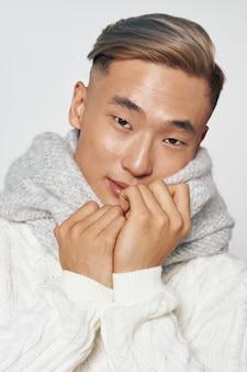 Asiatischer mann in der warmen winterkleidung, die im studio auf einer farbigen oberfläche aufwirft