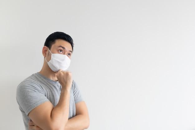 Asiatischer mann in der weißen maske, die den leeren kopienraum auf lokalisiertem hintergrund darstellt.