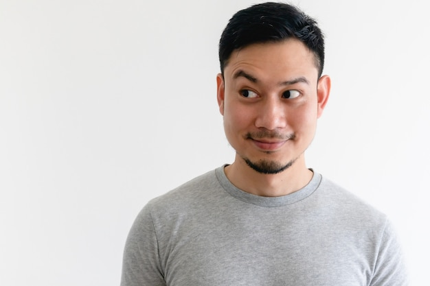 Asiatischer mann in einem grauen t-shirt betrachtet den leeren raum auf isoliertem weiß.