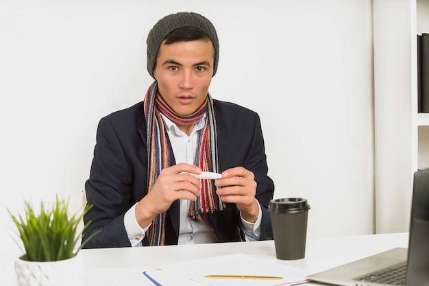 Asiatischer mann in einem hutschal und einer jacke messen die temperatur mit einem thermometer im büro