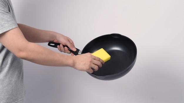 Asiatischer mann in grauer farbe t-shirt, das die antihaftpfanne mit handlichem geschirrspülschwamm säubert, die gelbe farbe auf der weichen seite und grün auf der harten seite für hygiene nach dem kochen