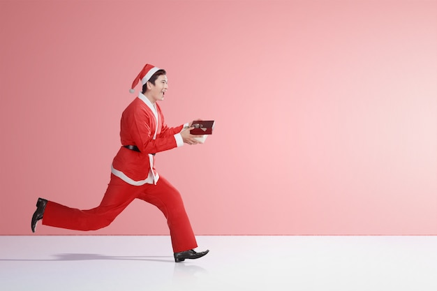 Asiatischer mann in laufendem sankt-kostüm beim halten der geschenkbox