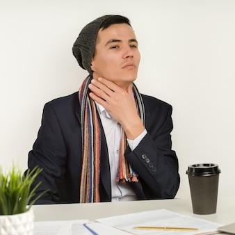 Asiatischer mann in mütze, schal und jacke hat halsschmerzen. angina im büro seit defekter heizung oder kühlung der klimaanlage übermäßig