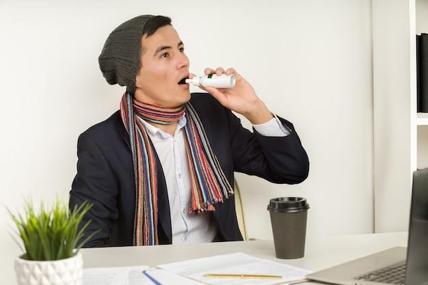 Asiatischer mann in mütze, schal und jacke verwendet ein spray im büro seit defekter heizung oder kühlung der klimaanlage