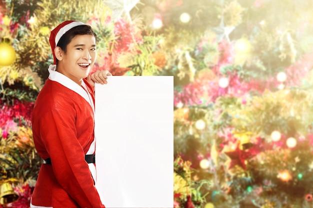 Asiatischer mann in sankt-kostüm, das ein weißes brett mit einem verzierten weihnachtsbaum hält