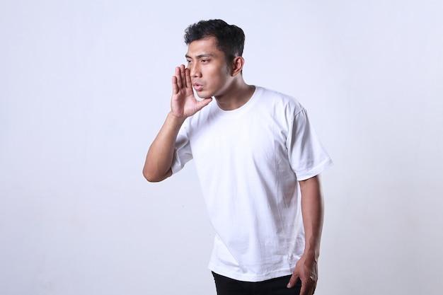 Asiatischer mann in weiß mit einem flüsternden ausdruck auf weißem hintergrund