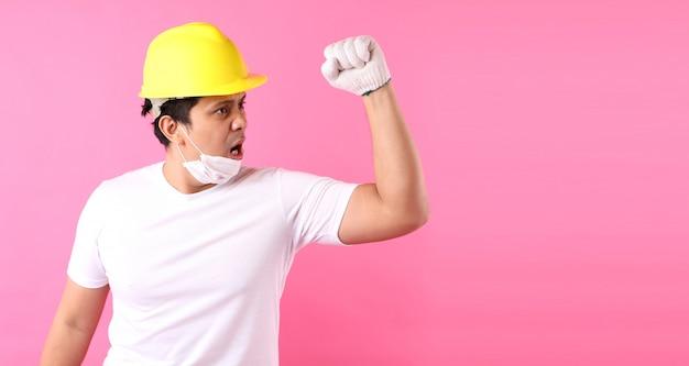 Asiatischer mann industriearbeiter oder ingenieur, der einen architektenbauer arbeitet glücklich aufgeregt, seine fäuste im studio zu heben mit kopierraum, konzept internationaler arbeitstag.