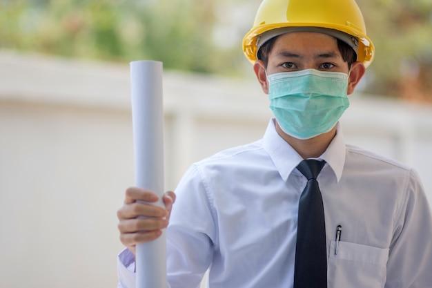 Asiatischer mann ingenieur ein tragender gesichtsmasken gelber schutzhelm mit blaupause arbeiten professionelles bauarchitektenprojekt