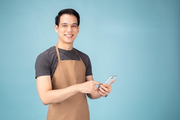 Asiatischer mann-inhaber, der mit smartphone steht