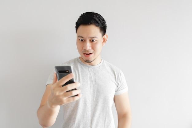 Asiatischer mann ist mit der anwendung im smartphone zufrieden.