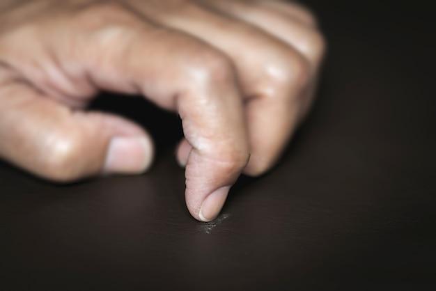 Asiatischer mann kratzte wegen stress mit dem fingernagel am tisch. symptome depression
