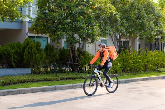 Asiatischer mann kurier auf fahrrad liefert lebensmittel in den straßen der stadt mit einer lieferung von warmen lebensmitteln von take aways und restaurants nach hause, express lebensmittel lieferung und online-shopping-konzept.