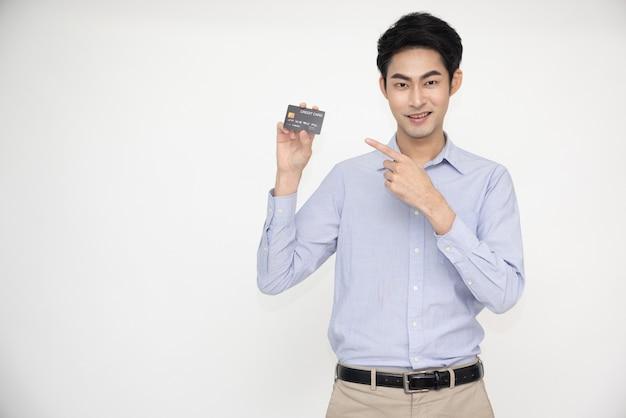 Asiatischer mann lächelnd, der eine kreditkarte für die zahlung oder das bezahlen von online-geschäften vorlegt